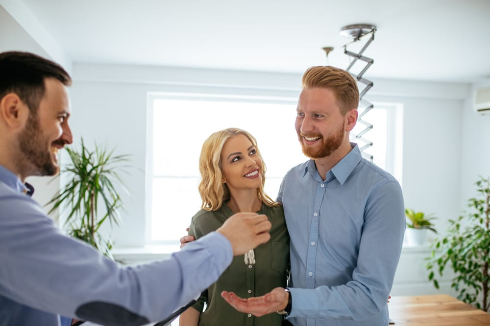 A young couple stands in a bright room as a man hands them house keys.