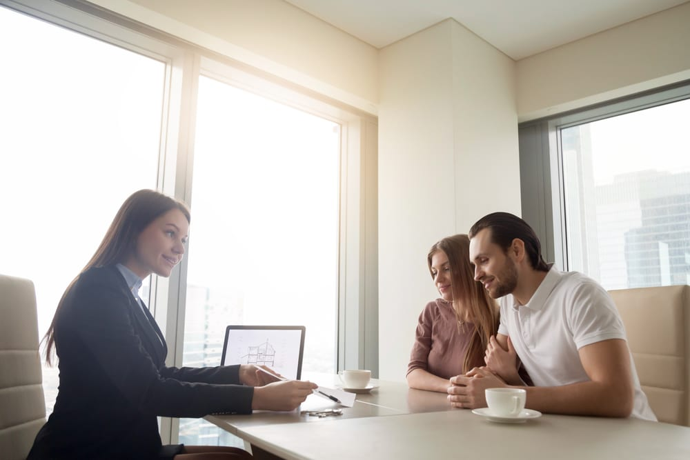 A couple talking to a lender across a table in a bright room.