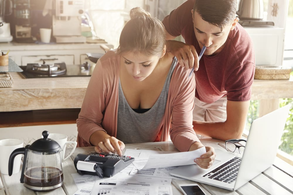 Young couple reviewing finances at home using calculator and laptop