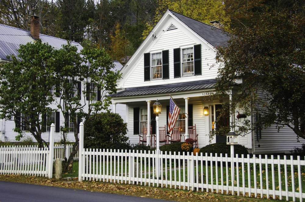White clapboard house with a white picket fence and American flag