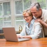 Senior couple using the laptop together at home in the kitchen