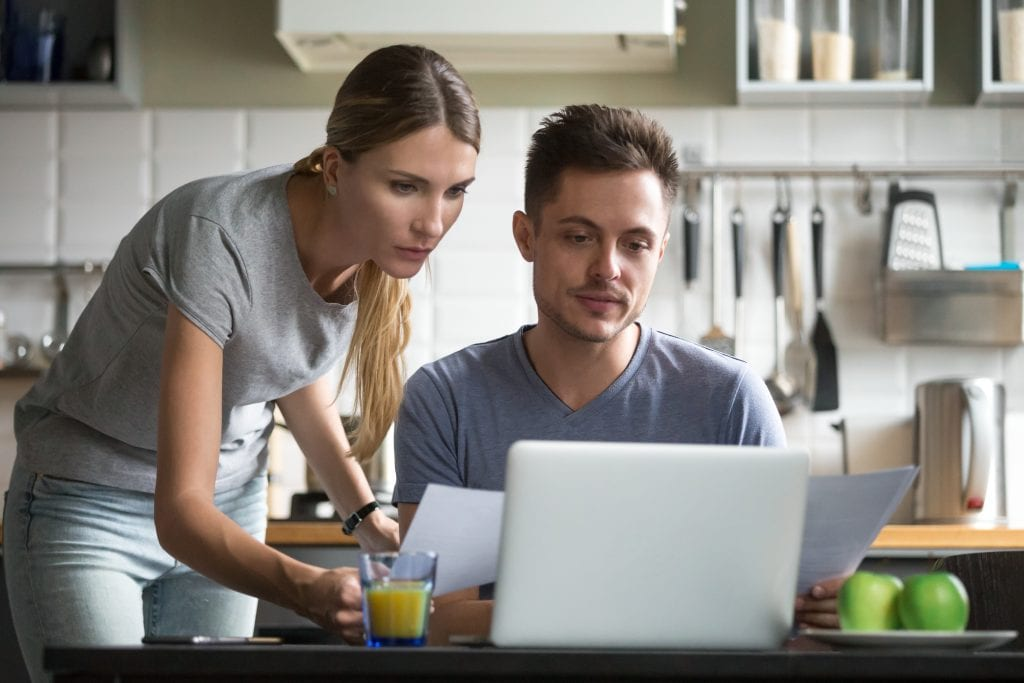 Young couple looking at laptop, holding papers, applying for a loan