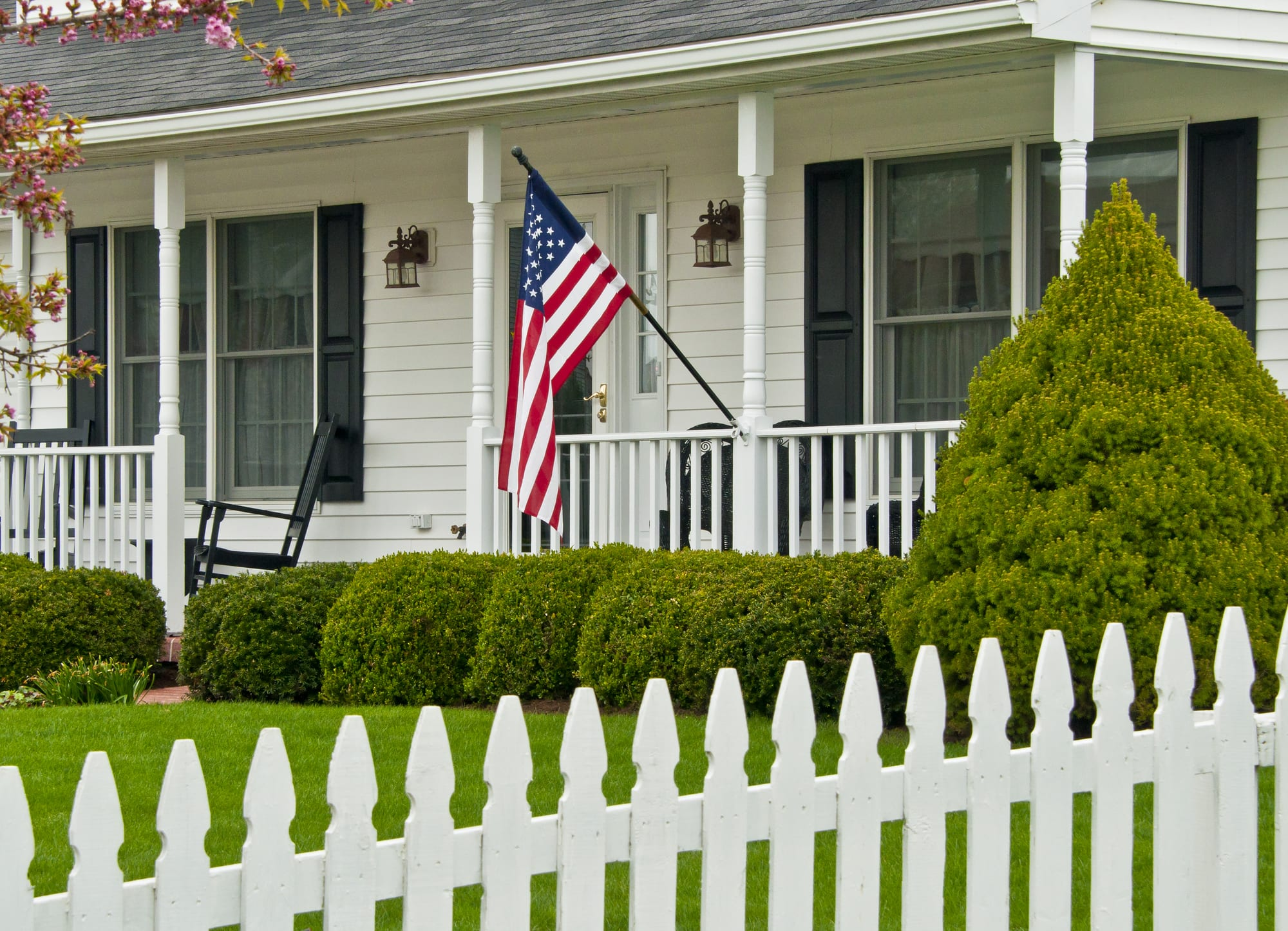 American flag hanging from classic house with white picket fence