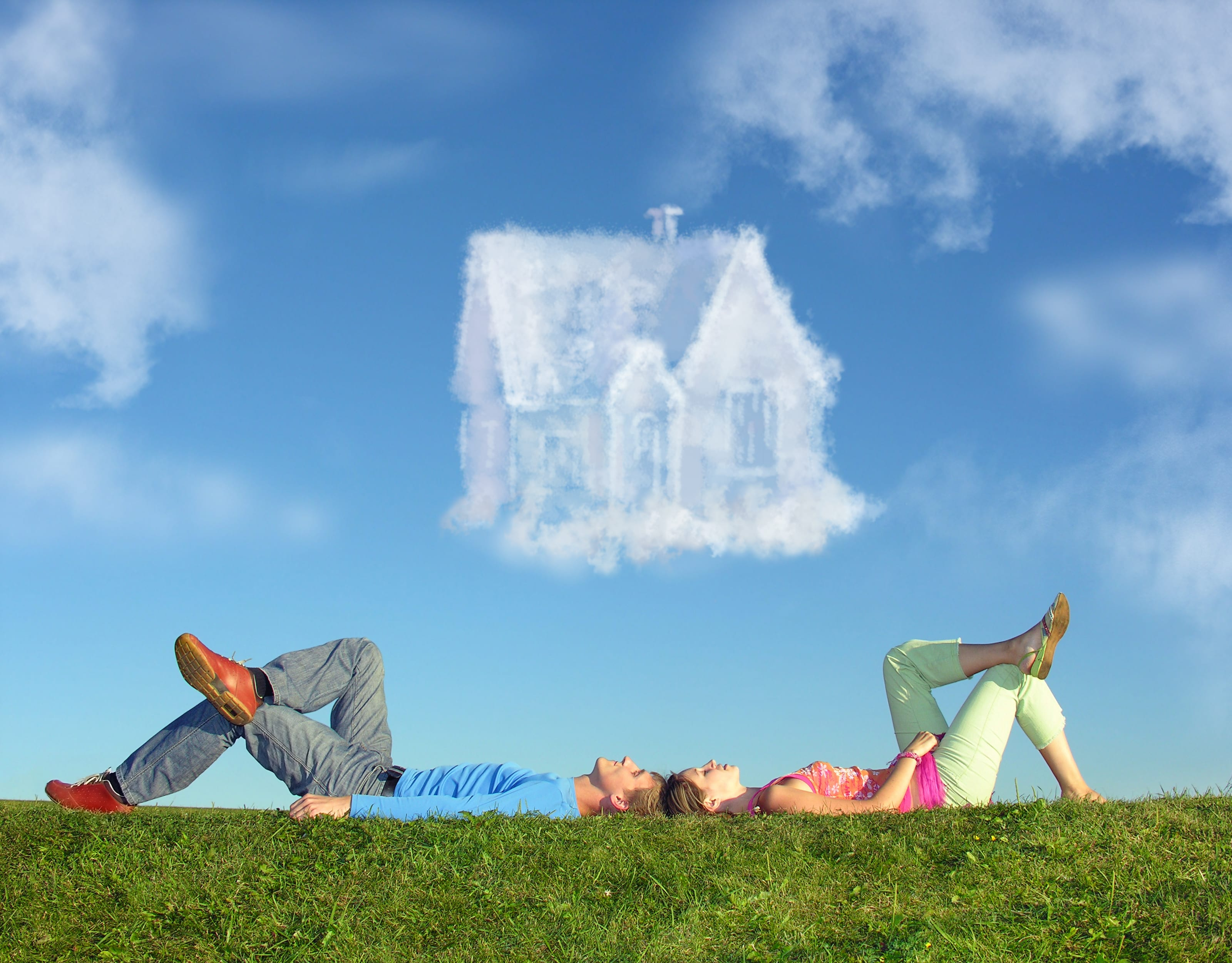 young couple lying on grass, house-shaped cloud in the sky