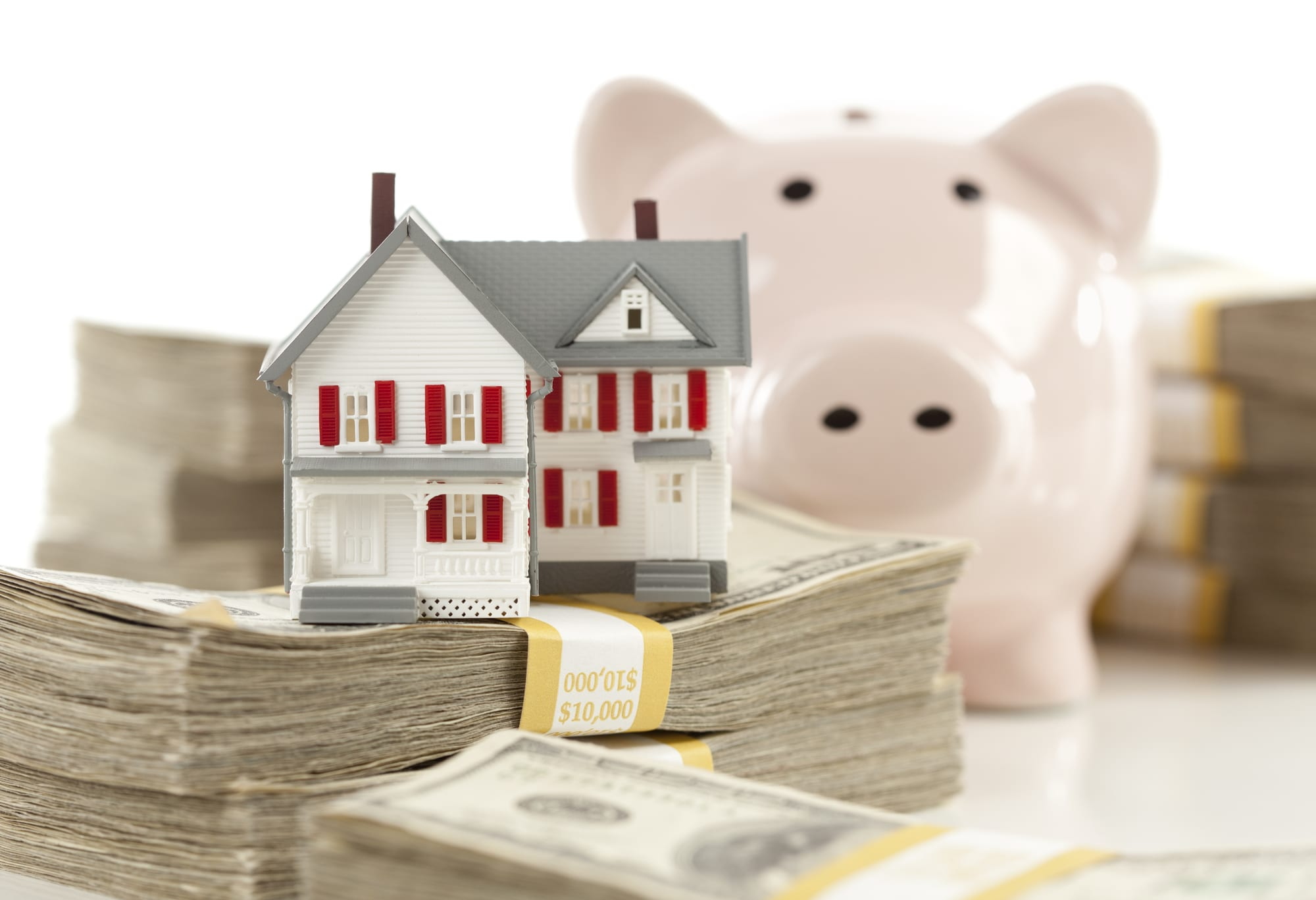 small model of house on stacks of cash, piggy bank behind