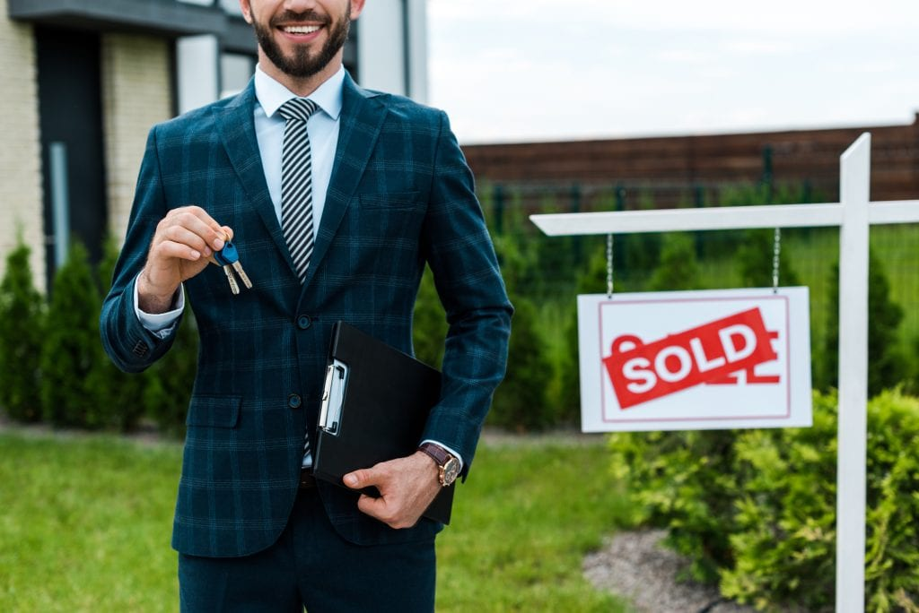 Cropped Realtor Estate Agent Holding Keys in Front of House with a Sold Sign
