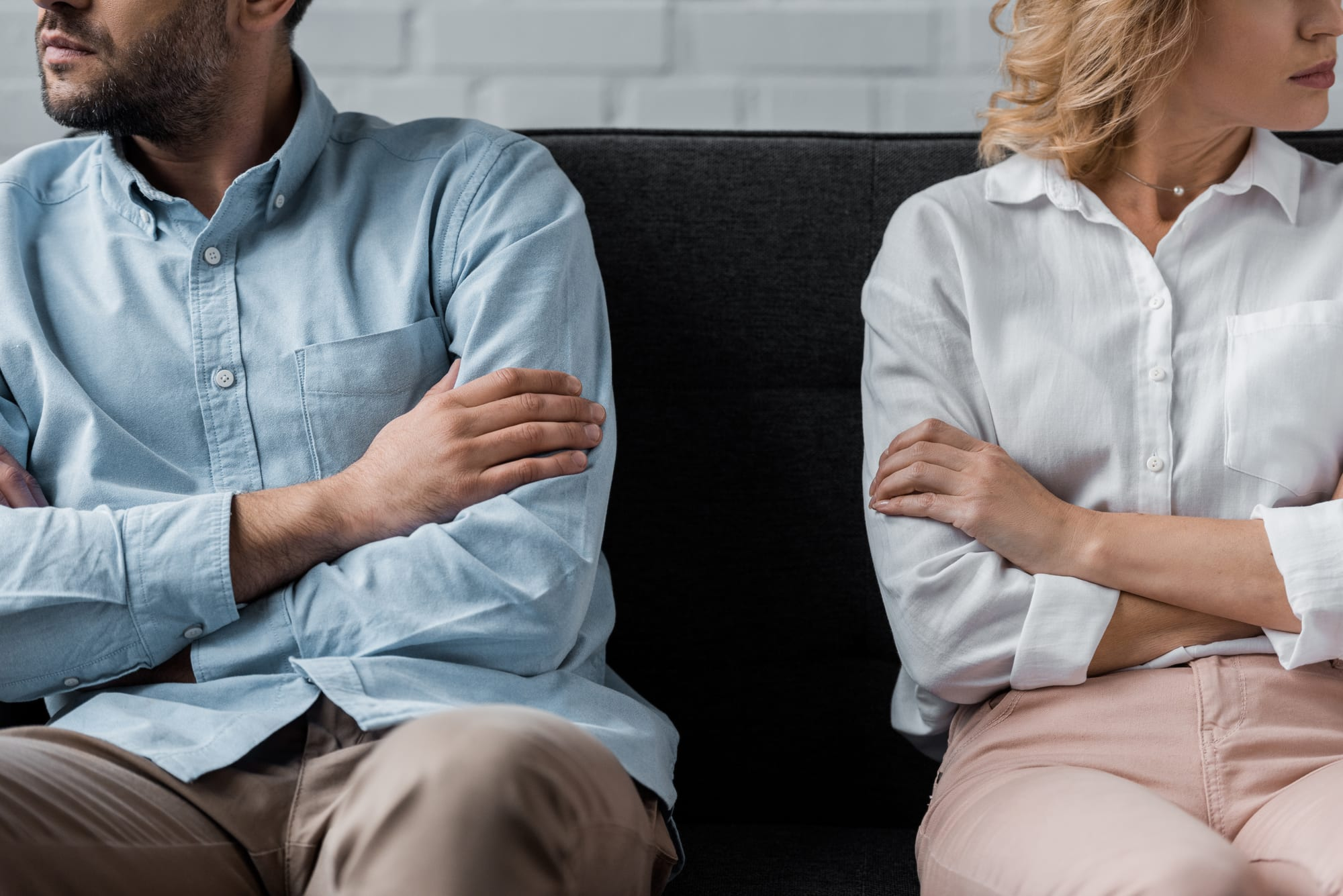 Cropped photo of man and woman on couch, arms crossed, looking away from each other