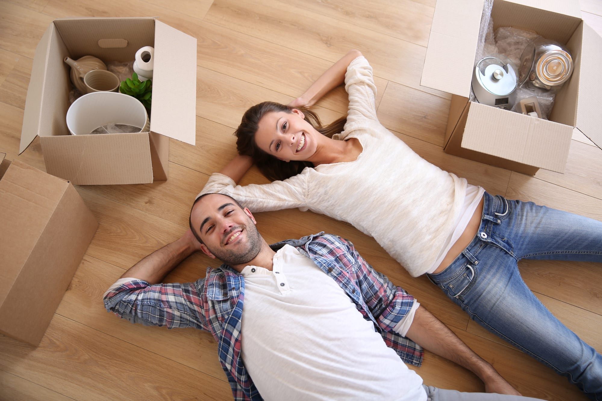 Young, smiling couple lying on floor at home by moving boxes