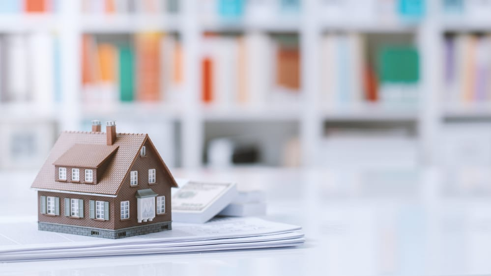 House Model on Stack of Papers