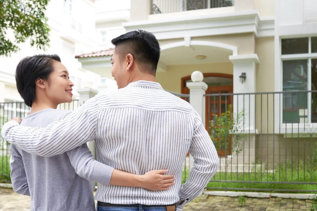Husband and wife smiling at each other in front of house