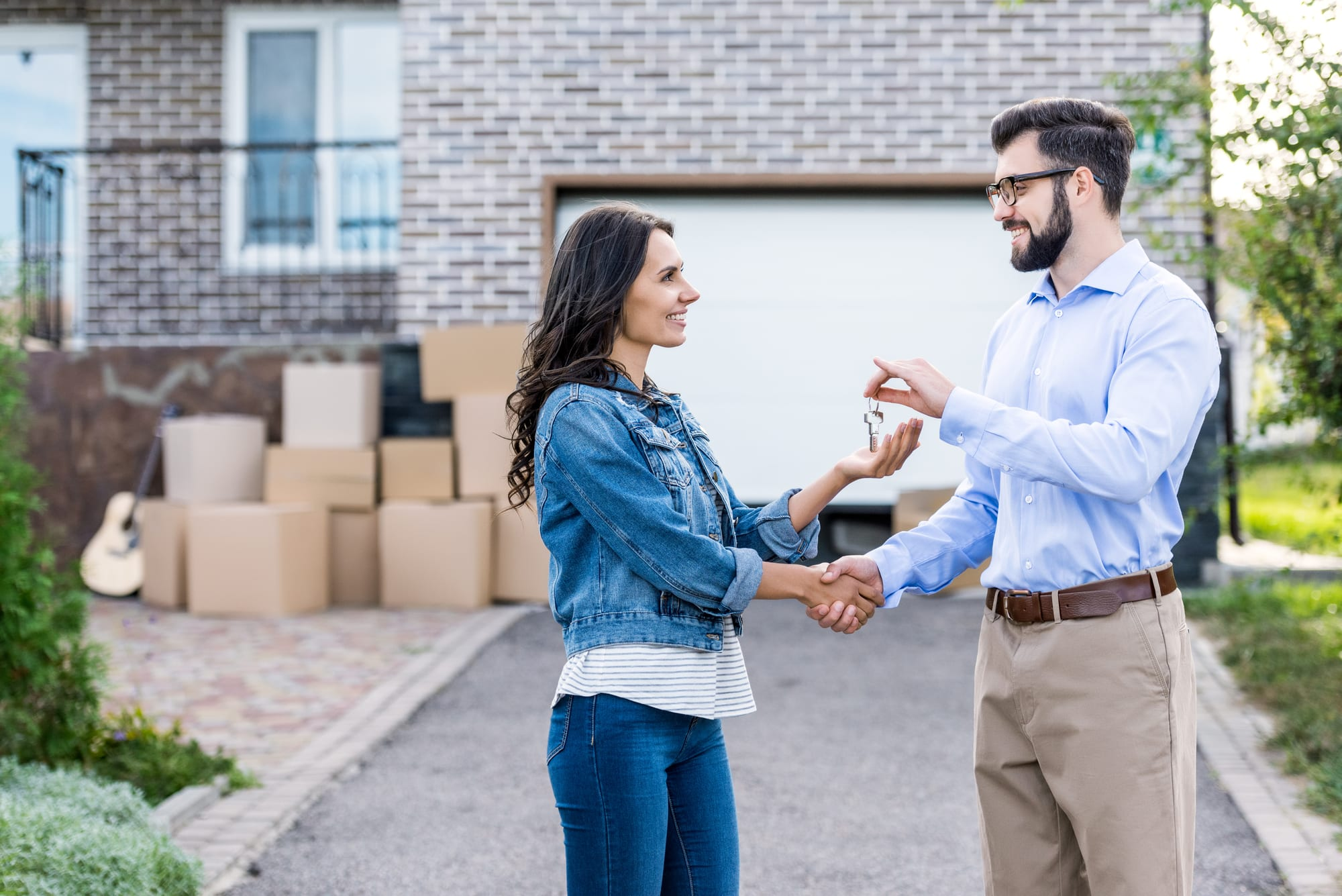 Woman shaking hands with man in front of house, he hands her house keys
